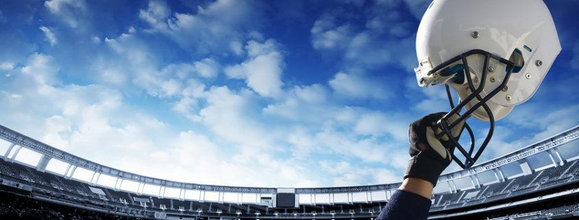 bigstock-Football-Player-raises-his-hel-22822439-845x321